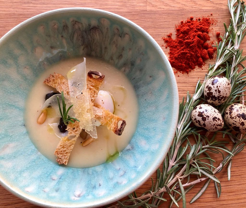 White Bean and Bacon Soup with Poached Quail Egg and Rosemary Flower Oil